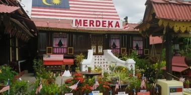 Casa de madera con la bandera malaya pintada en el tejado