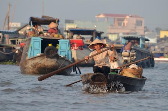 Los mercados flotantes son un trajín de remos, motores, verduras, frutas y dinero