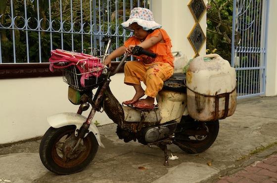 Una niña jugando con una antigua motocicleta