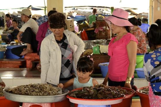 Niña vietnamita en el mercado del pescado