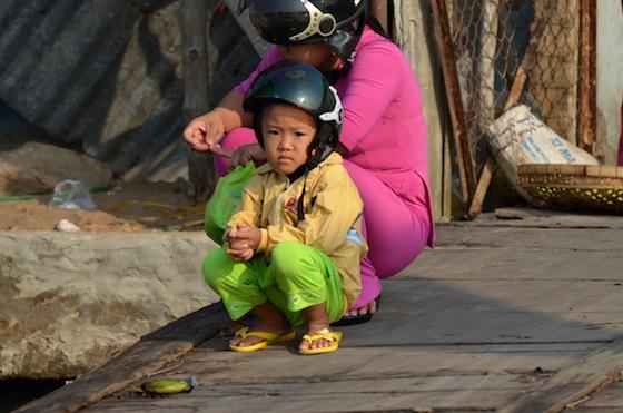 Un niño vietnamita descansando con el casco puesto al borde del Mekong