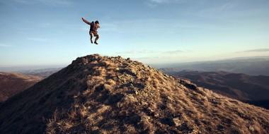 Saltando sobre la cima de una montaña